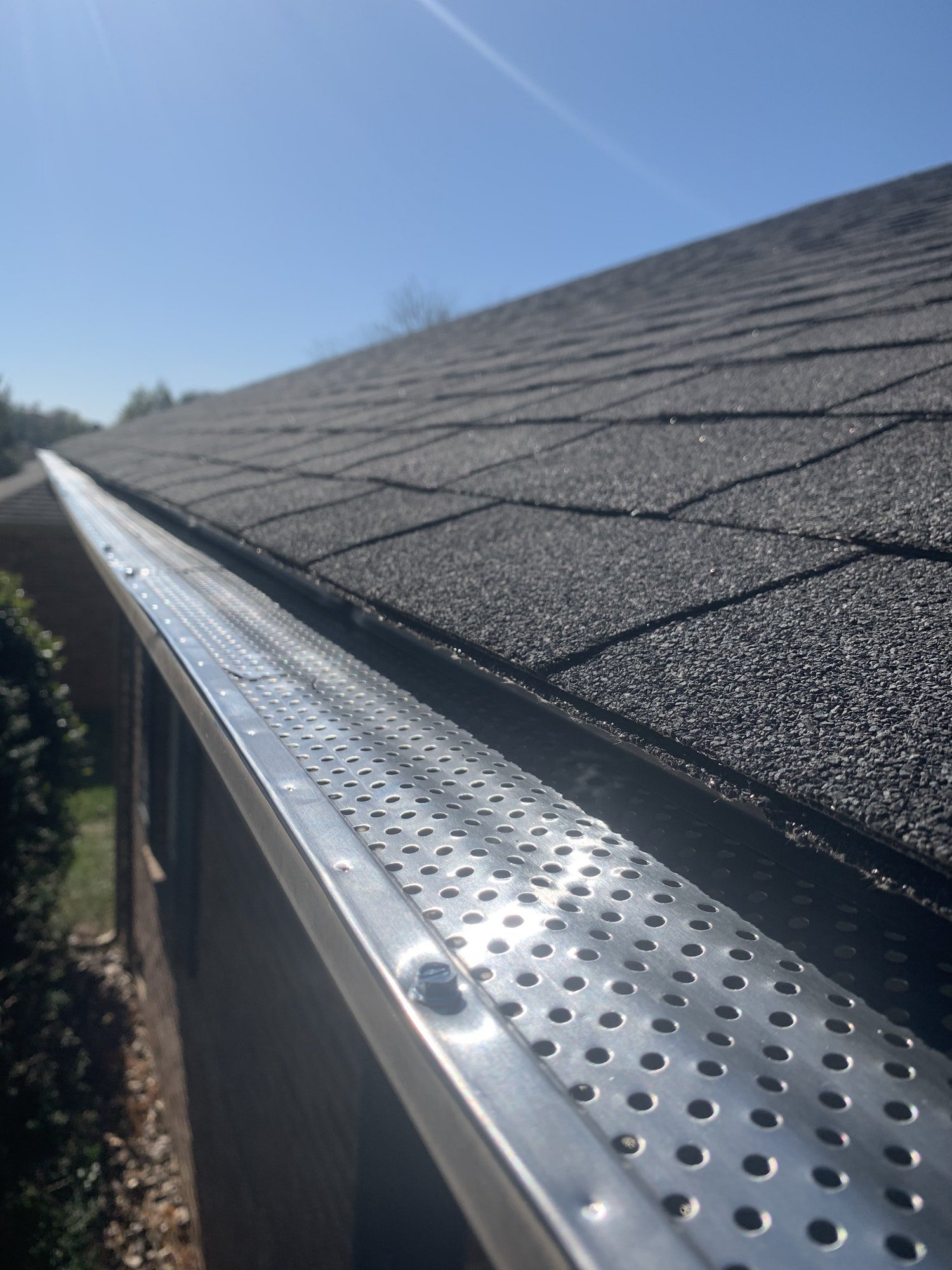Roof of a house showing gutter and gutter guard protection against leaves